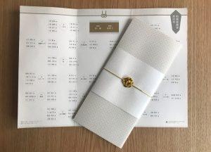 金色の水引梅結びを席次表に取付